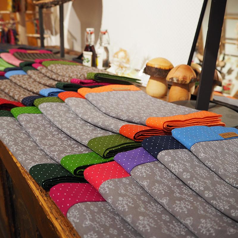 graue loopschals mit farbigen stoffvarianten zusammengelegt dargestellt