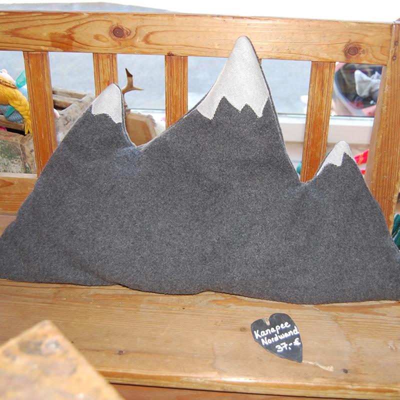 graues Kissen in Form einer Bergkette mit weißen Gipfeln